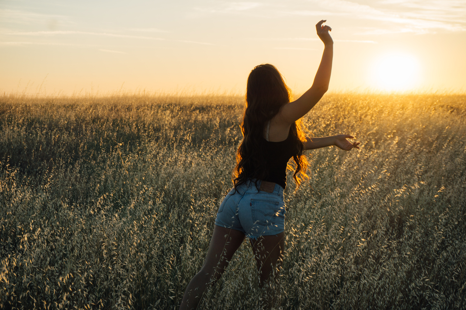 A woman dancing in a meadow at sunset