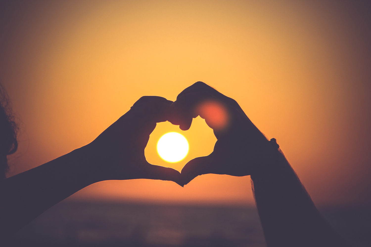 Two hands making a heart shape around a sunset.