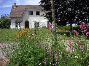 Image of a white cottage with wildflowers in front.