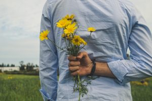 A man in a blue shirt holding flowers behind his back