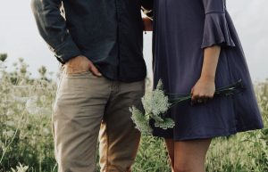 A man and a woman standing in a field, holding wildflowers