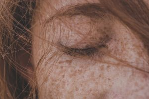 A closeup of a woman with red hair and freckles